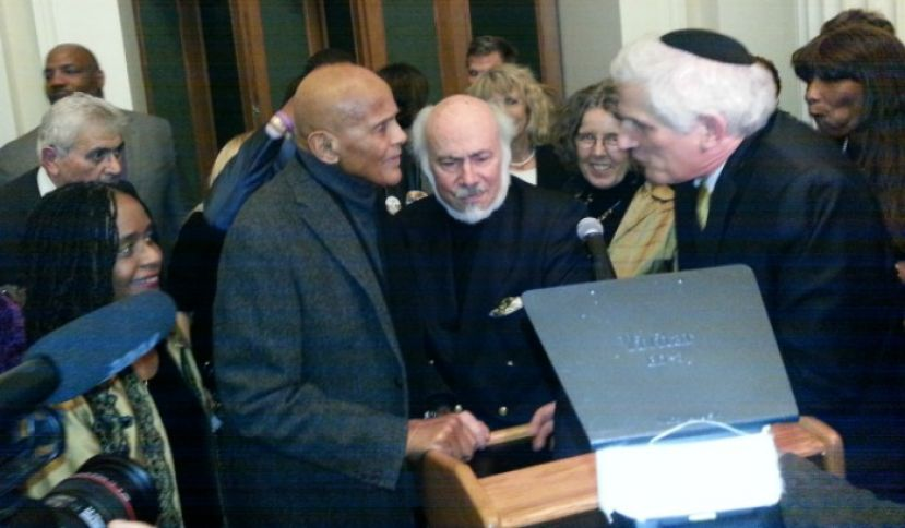 "Actor Harry Belafonte (left) and social relevant photographer, Stephen Somerstein (center), overwhelmed by reception guests after giving opening remarks to mark the opening of Somerstein's exhibit, ""The 1965 March: Freedom's Journey from Selma to Montgomery"" at the New York Historical Society"