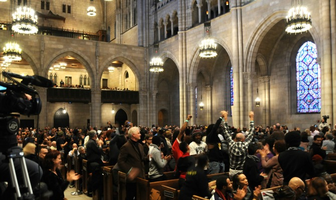 Bob-Avakia Cornel-West Dialogue Riverside-Church-Interior Crowd-in-pews-and-raised-fists-and-arms 11152014 Photo-Credit RevCom 670x400