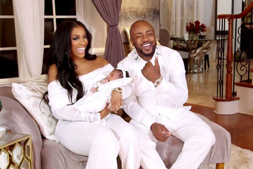 Porsha Williams of the Real Housewives of Atlanta holding baby, Pilar Jhena, and sitting with her fiance, Dennis McKinley