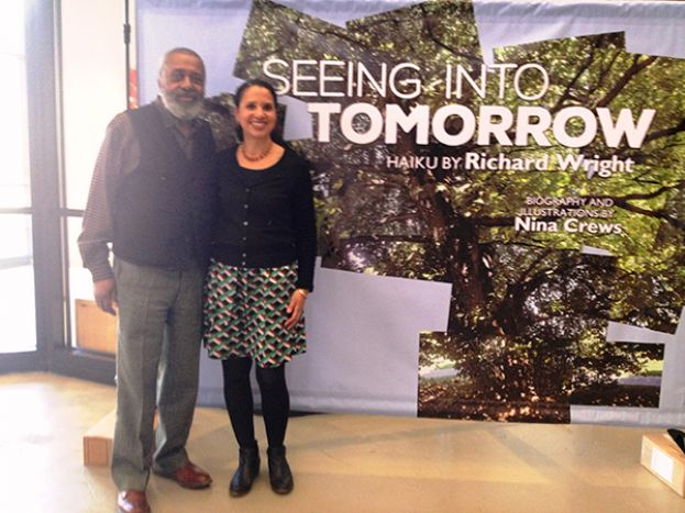 Nina Crews (r), with her father, Donald Crews, standing in front of a sign depicting her book, Seeing Into Tomorrow: Haiku by Richard Wright