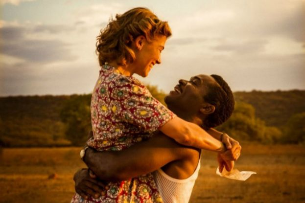 Actor, David Oyelowo, lifts and embraces actress Rosamund Pike, in the movie, A United Kingdom.