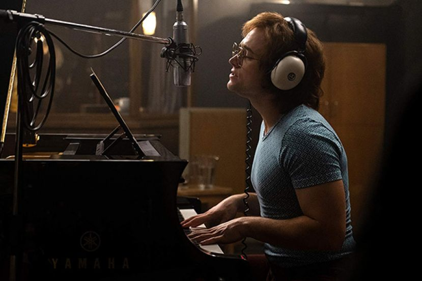 Taron Egerton playing the piamo, as Elton John, in the movie, Rocketman